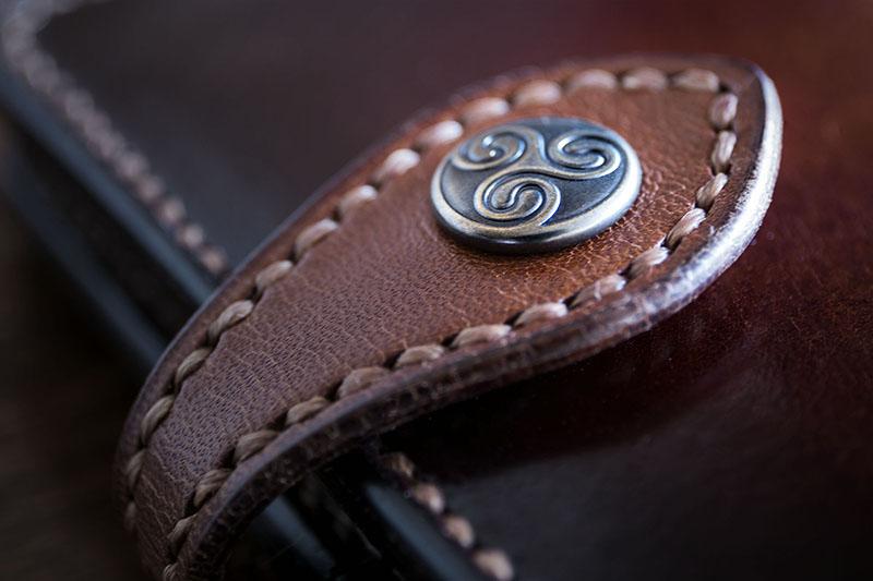 Detalle de cierre de cartera de cuero con broche con motivo celta